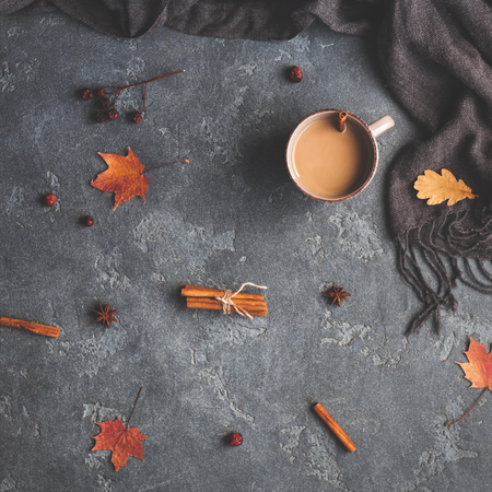 Autumn composition. Cup of coffee, scarf, autumn leaves on black background. Flat lay, top view, square Archivio Fotografico