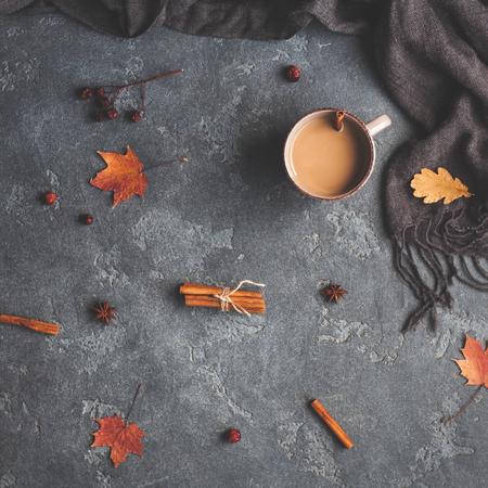Herfstsamenstelling. Kopje koffie, sjaal, herfstbladeren op zwarte achtergrond. Plattegrond, bovenaanzicht, vierkant Stockfoto