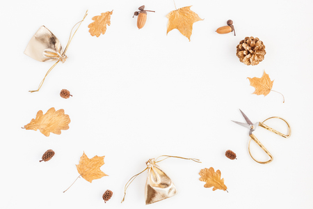 秋季構圖。禮物,秋天金色的葉子,松果錐,在白色背景上的配件。平躺,頂視圖,副本空間