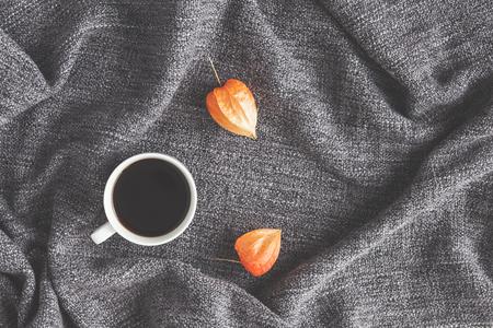 秋季構圖。一杯咖啡,在布料背景上的秋天的花朵。平躺,頂視圖