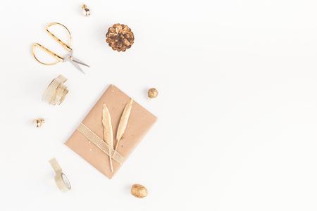 Рождественская композиция. Рождественский подарок, сосновый конус, золотые аксессуары на белом фоне. Квартира, вид сверху, место для копирования
