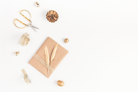 Christmas composition. Christmas gift, pine cone, golden accessories on white background. Flat lay, top view, copy space