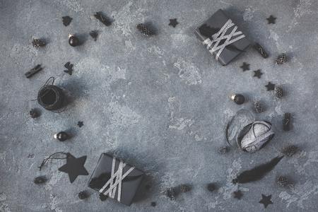 Рождественская композиция. Рождественские подарки, сосновые шишки, черные аксессуары на темном фоне. Квартира, вид сверху, место для копирования