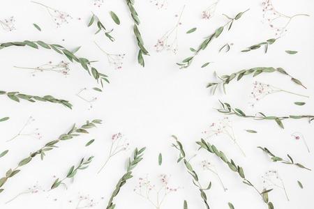 Skład kwiatów. Rama wykonana z różowych kwiatów i oddziałów eukaliptusa na białym tle. Płaski, górny widok, miejsce na kopię