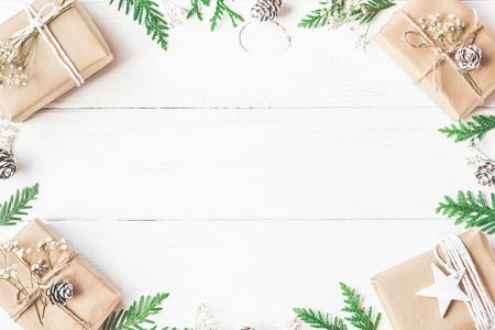 聖誕組合。框架由聖誕節禮物,松果錐,在白色木背景的thuja分支。平躺,頂視圖,副本空間