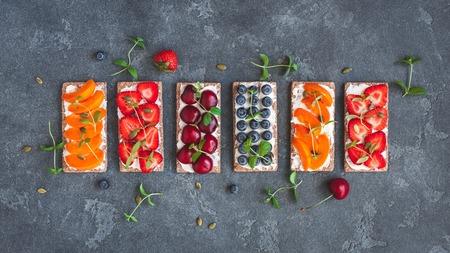 Merienda con pan crujiente, queso crema y frutas frescas. Concepto de alimentos saludables. Vista plana