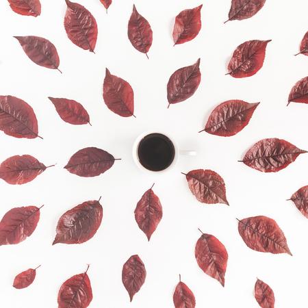 秋季構圖。一杯咖啡,在白色背景上的秋天紅色的葉子。平躺,頂視圖,廣場