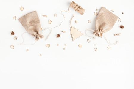 Рождественская композиция. Рождественские подарки, сосновые шишки, деревянные аксессуары на белом фоне. Квартира, вид сверху, место для копирования Фото со стока