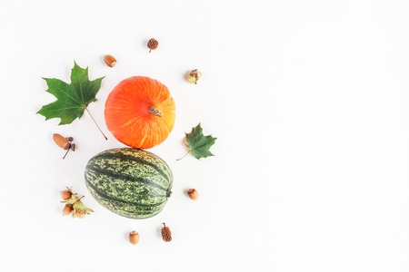Autumn composition made of pumpkins, maple tree leaves, hazelnuts on white background. Autumn, fall, thanksgiving concept. Flat lay, top view, copy space
