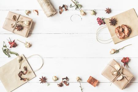Jesienna kompozycja. Ramki z prezentem, torby papierowe, jesienne liście, gwiazdki anyżkowe, suszone kwiaty. Przestrzeń robocza. Widok z góry, płaski