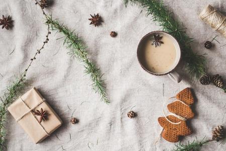 Composición de Navidad. Taza de café, regalo, ramas de alerce, palitos de canela, estrella de anís, galletas de Navidad. Vista superior, plano