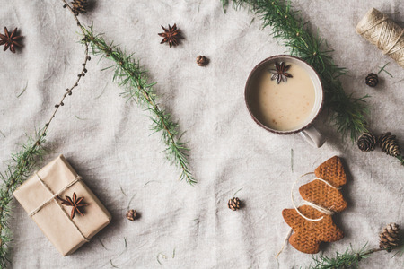 Kompozycja świąteczna. Filiżanka kawy, prezent, modrzewi gałązki, pałeczek cynamonu, anyż gwiazda, ciasteczka świąteczne. Widok z góry, płaski