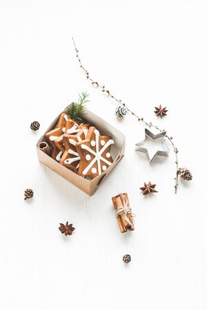 Christmas composition. Gift, larch branches, cinnamon sticks, anise star, christmas cookies. Top view
