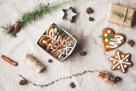 Kompozycja świąteczna. Dar, gałęzie modrzewi, pałeczek cynamonu, anyż gwiazda, ciasteczka świąteczne. Widok z góry, płaski