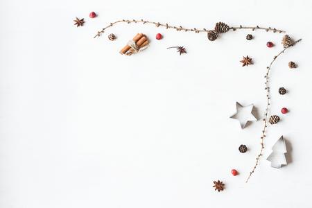 Kompozycja świąteczna. Gałęzie modrzewi, pałeczek cynamonu, gwiazda anyżkowa, żurawina suszona. Ramki świąteczne. Płaski, górny widok