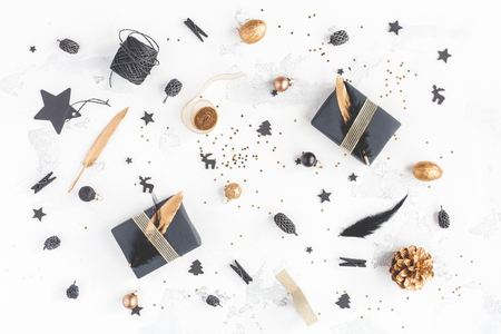 Christmas composition. Christmas gifts, pine cones, black and golden decorations on white background. Flat lay, top view 스톡 콘텐츠