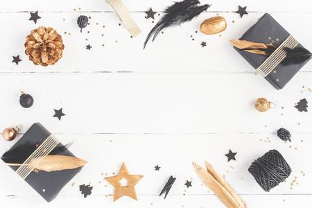 Composición de navidad Regalos de Navidad, conos de pino, decoraciones negras y doradas sobre fondo blanco de madera. Endecha plana, vista superior, espacio de copia Foto de archivo