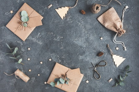 Christmas composition. Christmas gifts and eucalyptus branches on black background. Flat lay, top view, copy space