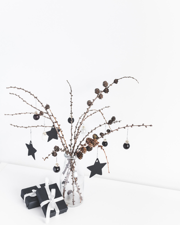 Christmas composition. Gifts, larch branches and black decorations on white. Christmas, winter, new year concept