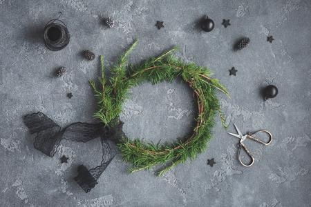 Kerst samenstelling. Met de hand gemaakte Kerstmiskroon, zwarte decoratie op donkere achtergrond. Bovenaanzicht, plat leggen Stockfoto