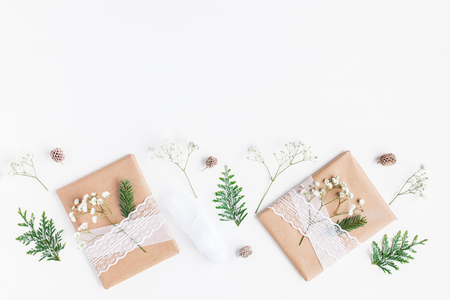 Christmas composition. Christmas gifts, pine cones, gypsophila flowers, thuja branches on white. Flat lay, top view, copy space