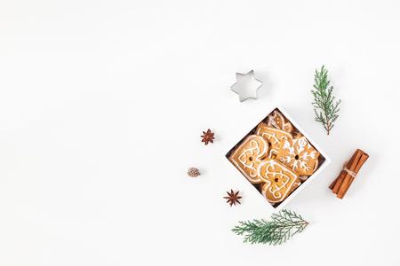 クリスマスの組成物。クリスマスのジンジャーブレッド クッキーと白い背景の上の松の枝。コピー スペース フラット横たわっていた、トップ ビュ 写真素材