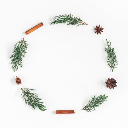 Kerst samenstelling. Kerstmiskroon van pijnboomtakken, pijpje kaneel, anijsplantsterren wordt gemaakt op witte achtergrond die. Plat leggen, bovenaanzicht, kopie ruimte, vierkant