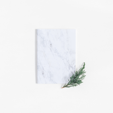 Christmas minimal composition. Marble notebook and pine branches on white. Christmas, winter, new year concept. Flat lay, top view, copy space, square