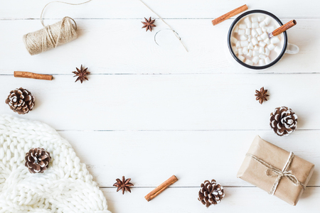 Christmas. Winter. Hot chocolate, cinnamon sticks, anise star, marshmallow, knitted blanket, gift and cones. Christmas composition. Flat lay, top view
