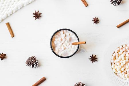 Рождество. Зима. Горячий шоколад, палочки корицы, анисовая звезда, зефир, трикотажное одеяло и конусы. Рождественская композиция. Плоский, вид сверху
