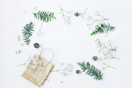 Christmas composition. Christmas gift, pine cones, thuja branches and gypsophila flowers. Top view, flat lay