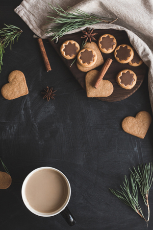 Christmas composition. Cup of coffee, christmas gingerbread, pine branch, cinnamon sticks, anise star. Flat lay, top view