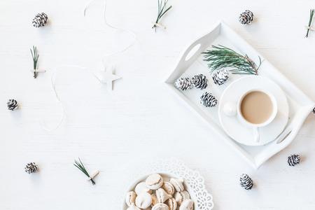 Weihnachtskomposition. Winterfrühstück. Tasse Kaffee, Kegel, Weihnachtsbaum Branchs. Draufsicht, flache Lage