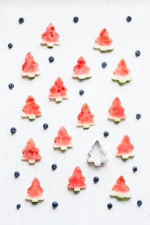 Weihnachtsmuster. Scheiben der Wassermelone in Form von Weihnachtsbäumen. Draufsicht, flache Lage