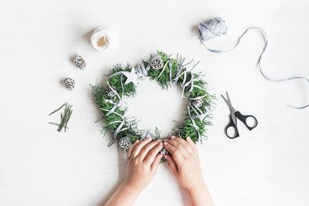 Christmas. Child making handmade christmas wreath. Top view, flat lay