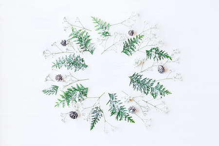 Winter frame made of pine cones, thuja branches and gypsophila flowers. Winter composition. Top view, flat lay