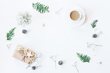 Weihnachtskomposition. Tasse Kaffee, Weihnachtsgeschenk, Tannenzapfen, Thuja Zweige und Gypsophila Blumen. Draufsicht, flache Lage