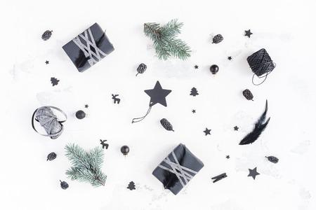 Weihnachtskomposition. Weihnachtsgeschenke, Kiefernkegel, Tannenzweige, schwarze Dekorationen auf weißem Hintergrund. Flache Lage, Draufsicht