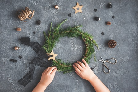 Christmas composition. Child making handmade christmas wreath on dark table. Top view, flat lay Foto de archivo