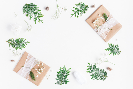 Christmas composition. Christmas gifts, pine cones, gypsophila flowers, thuja branches on white background. Flat lay, top view, copy space Foto de archivo