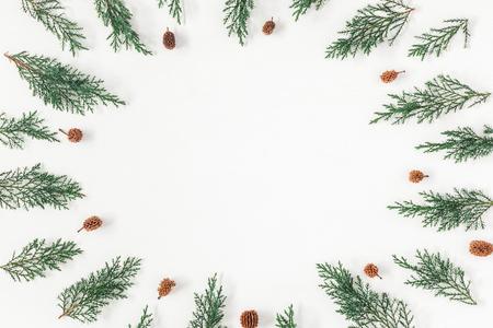 聖誕框架由松枝和松果在白色背景上。聖誕節,冬天,新的一年的概念。平躺,頂視圖,複製空間 版權商用圖片