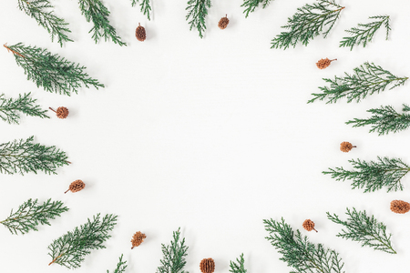 Christmas frame made of pine branches and pine cones on white background. Christmas, winter, new year concept. Flat lay, top view, copy space