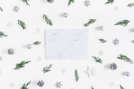 Christmas composition. Marble paper blank and pine branches on white background. Christmas, winter, new year concept. Flat lay, top view, copy space