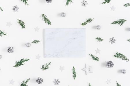 Weihnachtskomposition. Marmorpapierleerzeichen und Kiefernniederlassungen auf weißem Hintergrund. Weihnachten, Winter, Konzept des neuen Jahres. Flache Lage, Draufsicht, Kopie, Raum
