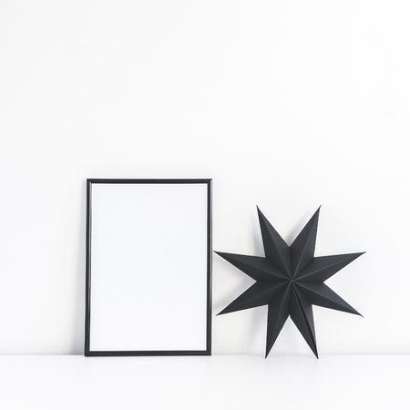 Christmas composition. Black frame and christmas star on white background. Front view, mock up, square, copy space