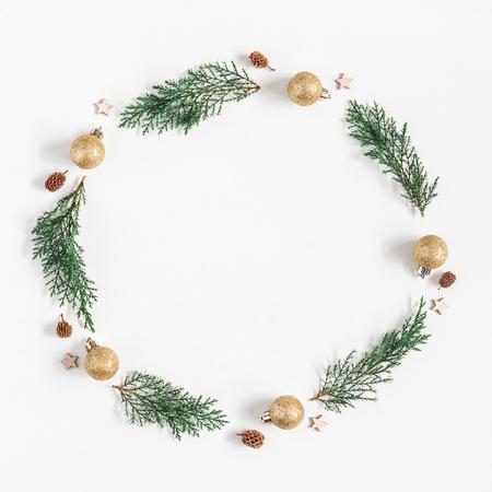 Composizione di Natale. Corona di Natale fatto di rami di pino, palle, conci di pino su sfondo bianco. Piatto piano, vista dall'alto, spazio di copia, quadrato