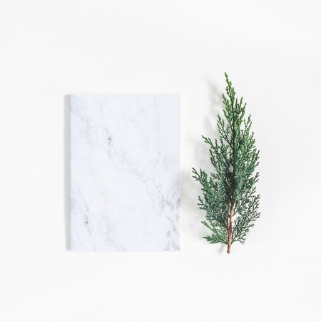 Christmas minimal composition. Marble notebook and pine branches on white background. Christmas, winter, new year concept. Flat lay, top view, copy space, square Zdjęcie Seryjne