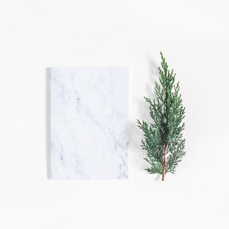 Weihnachtsminimaler Aufbau. Marmornotizbuch und Kiefernniederlassungen auf weißem Hintergrund. Weihnachten, Winter, Konzept des neuen Jahres. Flache Laien, Draufsicht, Kopie, Platz, Quadrat