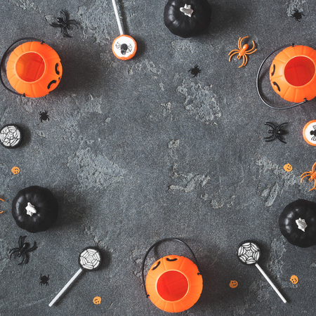 Halloween decorations. Decorative black and orange pumpkins on black background. Halloween concept. Flat lay, top view, copy space, square Zdjęcie Seryjne
