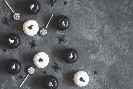 Décorations d'Halloween. Citrouilles décoratives noires et blanches sur fond noir. Concept d'Halloween. Plat poser, vue de dessus, espace copie Banque d'images